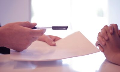 Mortgage papers held in hands with a pen, being handed to the other hands.