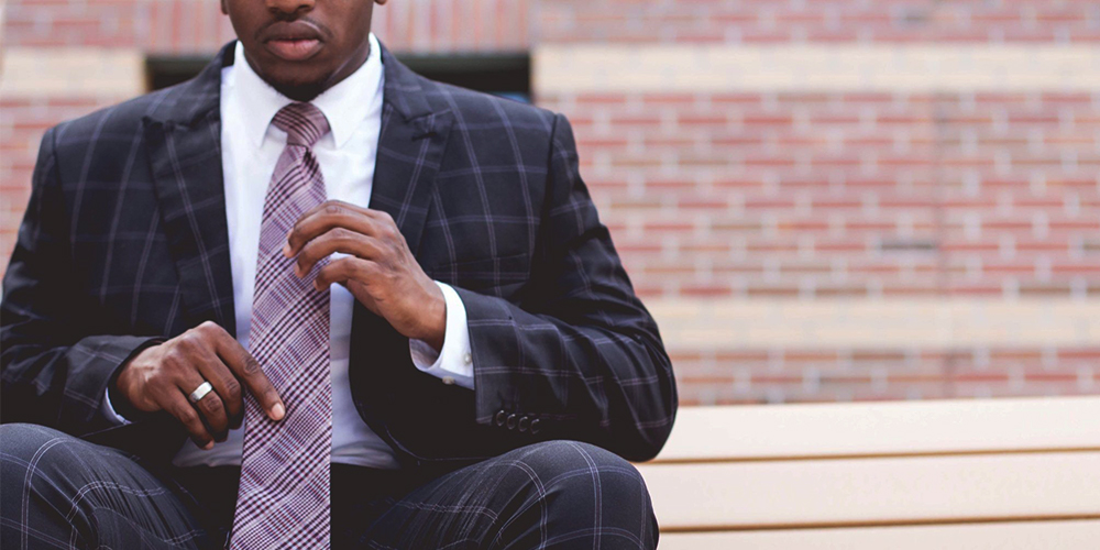 Black man in a suit seated with brick wall behind him.