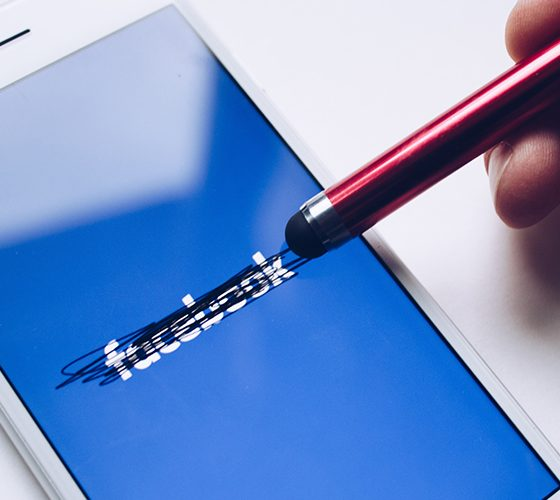 Facebook being crossed out by a stylus on a mobile device.