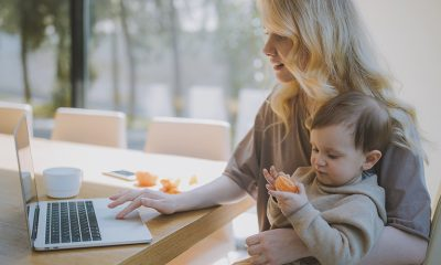 A woman holding a baby on her lap doing remote work.