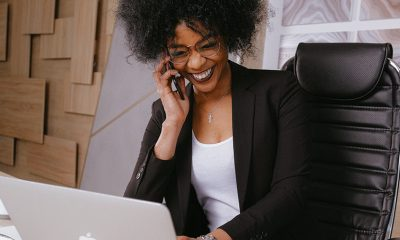 Black woman smiling in communication talking on phone and laptop in front of her.