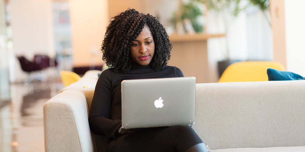 Black woman working on a laptop on a couch, running her small businesses' needs digitally.