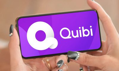 A mobile phone open to Quibi in feminine hands with decorated nails.