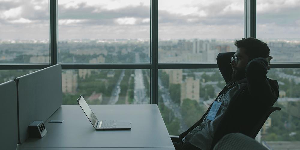 Stressed man facing laptop, one of many facing job losses
