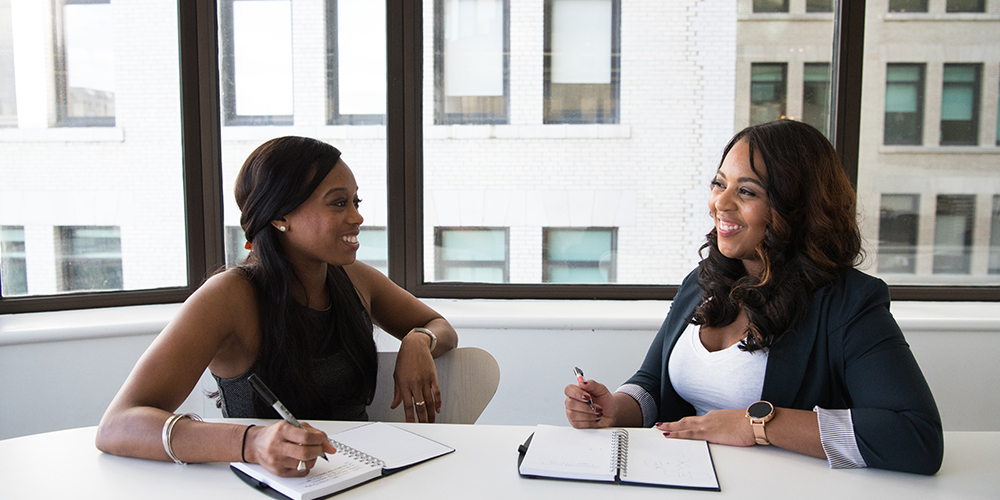 Two women at meeting table discussing small business.